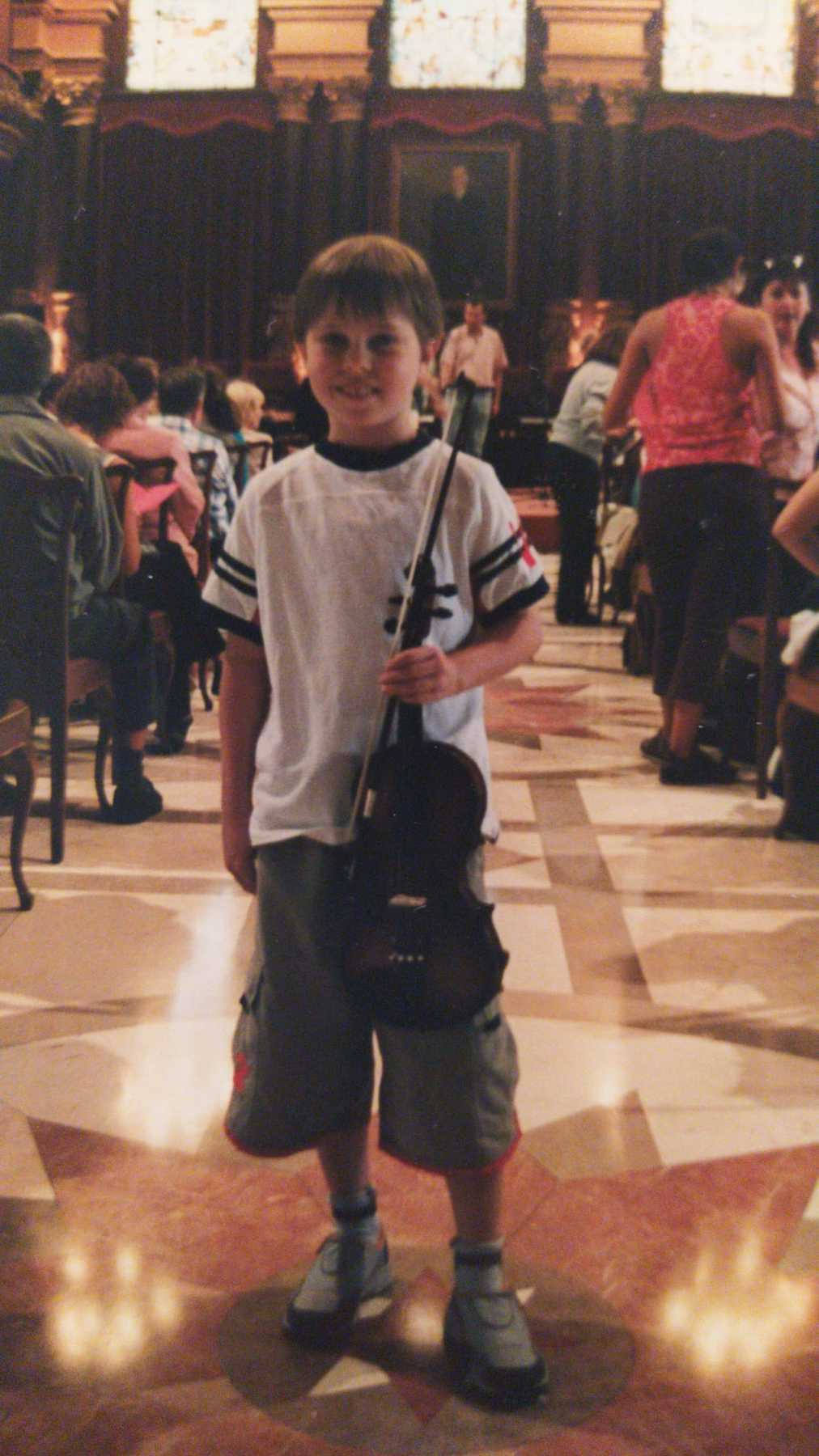 Young Sash about to play violin at town hall in Donostia